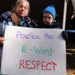 Two people holding up a sign Practice the R-word respect One has a disability