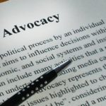 Advocacy and Pen - ballpoint pen and laying on top of the definition of advocacy